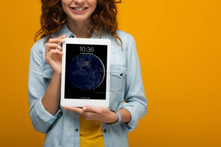 Photo for Cropped view of cheerful curly girl holding digital tablet with lock screen isolated on orange - Royalty Free Image