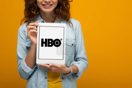 Photo for Cropped view of cheerful curly girl holding digital tablet with hbo app on screen isolated on orange - Royalty Free Image