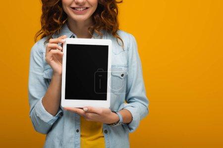 vista recortada de niña rizada alegre sosteniendo tableta digital con pantalla en blanco aislado en naranja
