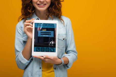 Photo pour Vue recadrée de fille bouclée gaie retenant la tablette numérique avec l'application de réservation sur l'écran d'isolement sur l'orange - image libre de droit