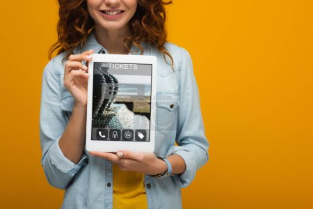 Photo for Cropped view of cheerful curly girl holding digital tablet with tickets app on screen isolated on orange - Royalty Free Image