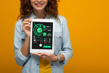 Photo for Cropped view of curly girl holding digital tablet with charts and graphs isolated on orange - Royalty Free Image