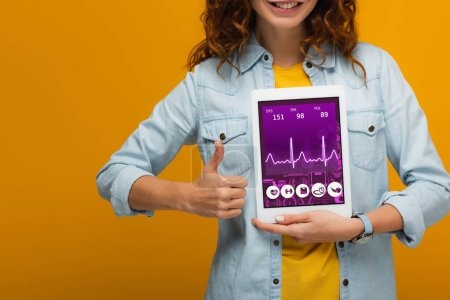 Photo for Cropped view of cheerful curly girl holding digital tablet with e health app screen and showing thumb up isolated on orange - Royalty Free Image