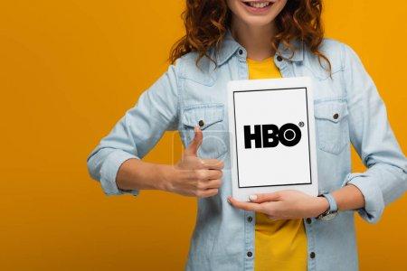abgeschnittene Ansicht eines fröhlichen lockigen Mädchens, das ein digitales Tablet mit Hbo-App-Bildschirm hält und den Daumen vereinzelt auf Orange zeigt