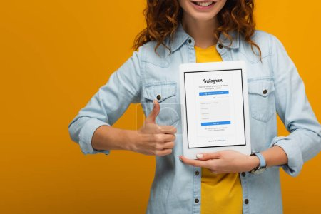 Photo for Cropped view of cheerful curly woman holding digital tablet with instagram app on screen and showing thumb up isolated on orange - Royalty Free Image
