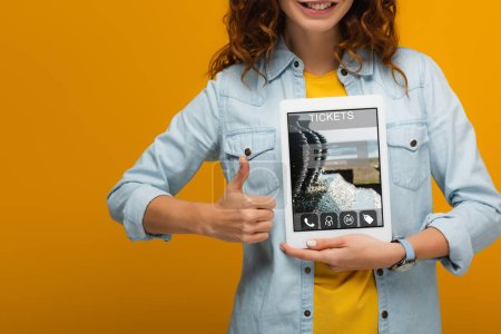 Photo for Cropped view of cheerful curly woman holding digital tablet with tickets app on screen and showing thumb up isolated on orange - Royalty Free Image