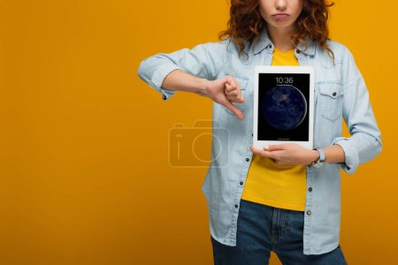 Photo for Cropped view of upset curly woman holding digital tablet with lock screen and showing thumb down on orange - Royalty Free Image