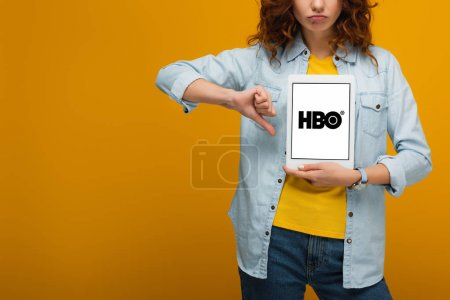 Photo for Cropped view of upset curly woman holding digital tablet with hbo app on screen and showing thumb down on orange - Royalty Free Image