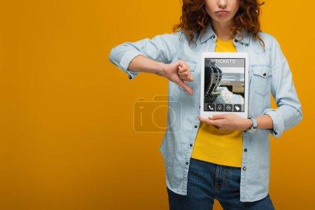 Photo pour Vue recadrée de femme bouleversée tenant tablette numérique avec l'application de billets à l'écran et montrant pouce vers le bas sur orange - image libre de droit