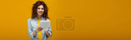 Photo for Panoramic shot of cheerful curly redhead girl looking at camera and holding digital tablet on orange - Royalty Free Image
