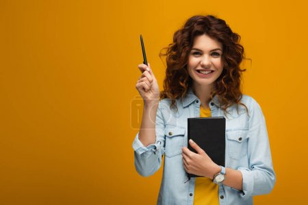 Photo for Happy redhead young woman holding notebook and pen on orange - Royalty Free Image