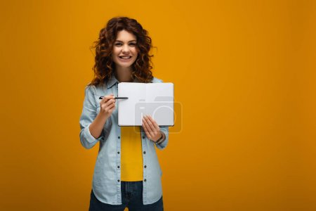 Photo for Smiling redhead young woman pointing at blank notebook with pen on orange - Royalty Free Image