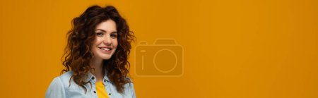 Photo for Panoramic shot of young curly woman looking at camera isolated on orange - Royalty Free Image