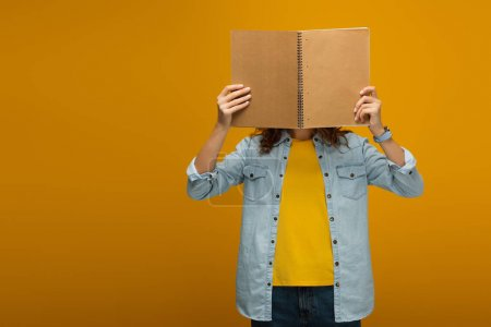 Photo for Young woman standing and covering face with notebook on orange - Royalty Free Image