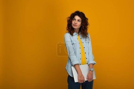 Photo for Beautiful pensive redhead girl holding laptop on orange - Royalty Free Image