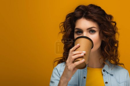 Photo for Curly redhead girl covering face with paper cup while drinking on orange - Royalty Free Image