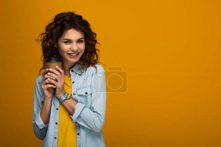 Photo pour Heureux bouclé rousse fille tenant tasse en papier tout en souriant sur orange - image libre de droit