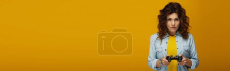 Photo for Panoramic shot of redhead woman biting lips while playing video game on orange - Royalty Free Image