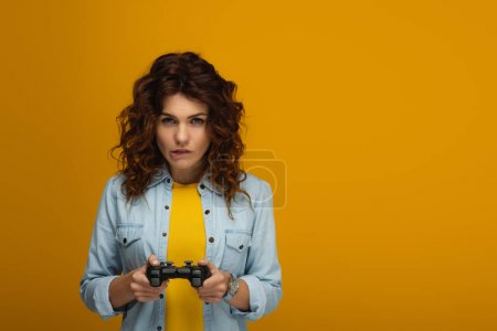 Photo for Curly redhead woman biting lips while playing video game on orange - Royalty Free Image