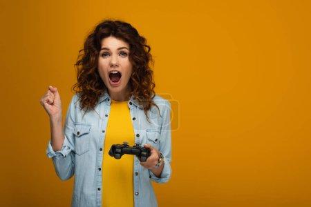 Photo pour Femme bouclée émotionnelle faisant des gestes et des cris tout en tenant joystick sur l'orange - image libre de droit