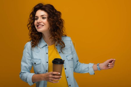 Photo for Happy curly redhead girl holding coffee to go isolated on orange - Royalty Free Image