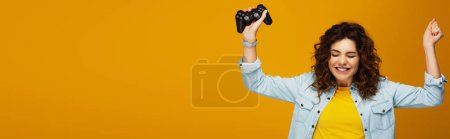 Photo for Panoramic shot of cheerful curly redhead girl gesturing while holding joystick on orange - Royalty Free Image