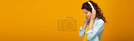 Photo pour Plan panoramique de fille rousse heureuse écoutant de la musique dans les écouteurs sur orange - image libre de droit