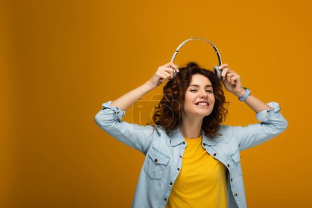 Photo for Happy redhead girl smiling while holding headphones on orange - Royalty Free Image