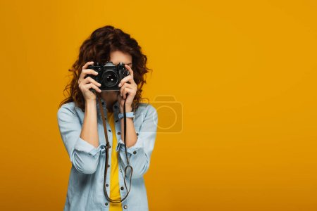 Photo for Curly redhead photographer covering face with digital camera isolated on orange - Royalty Free Image