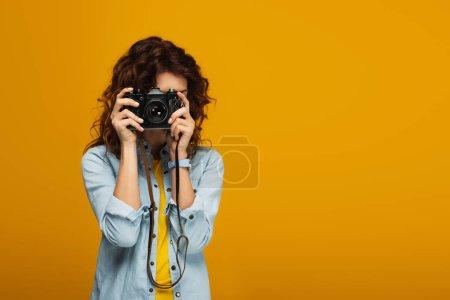 Photo pour Photographe bouclé de couverture de rousse couvrant le visage avec l'appareil-photo numérique d'isolement sur l'orange - image libre de droit