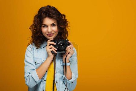 Photo pour Photographe bouclé de rousse retenant l'appareil-photo numérique d'isolement sur l'orange - image libre de droit