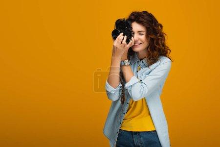 Photo for Happy redhead photographer taking photo while holding digital camera on orange - Royalty Free Image