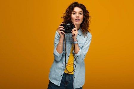 Photo pour Photographe de rousse attirante retenant l'appareil-photo numérique sur l'orange - image libre de droit