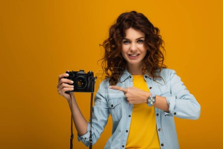 Photo for Cheerful redhead photographer pointing with finger at digital camera on orange - Royalty Free Image