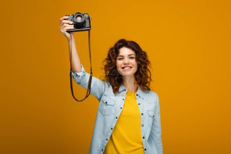 Photo for Cheerful redhead photographer holding digital camera above head on orange - Royalty Free Image