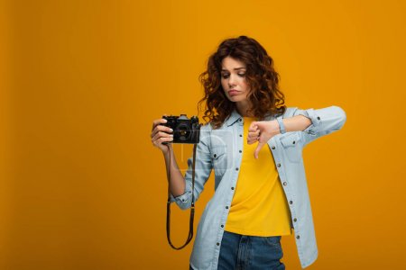 Photo for Upset redhead photographer holding digital camera and showing thumb down on orange - Royalty Free Image