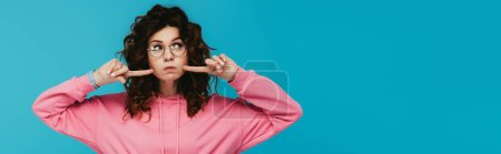 Photo pour Panoramic shot of curly redhead girl in glasses holding fingers near cheeks isolated on blue - image libre de droit