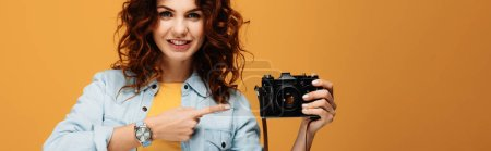 Photo for Panoramic shot of cheerful redhead photographer pointing with finger at digital camera on orange - Royalty Free Image