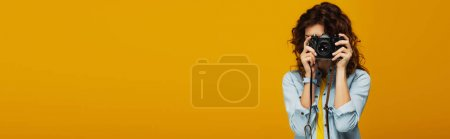 Photo pour Prise de vue panoramique du photographe rousse bouclé couvrant le visage avec appareil photo numérique isolé sur orange - image libre de droit