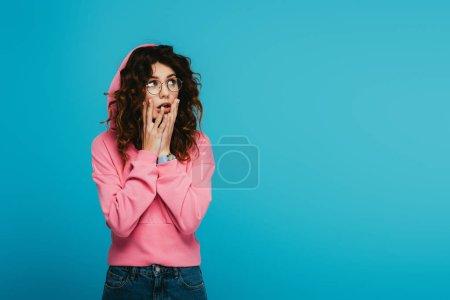 Photo pour Fille rousse surprise touchant le visage tout en restant sur le bleu - image libre de droit