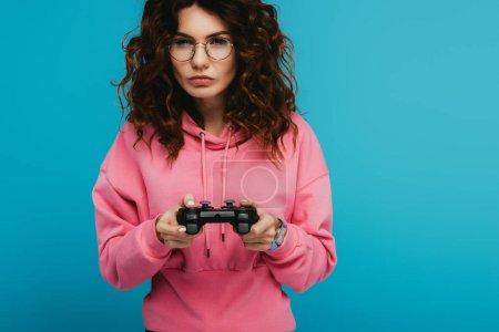 Photo pour Fille rousse bouclée sérieuse jouant au jeu vidéo tout en retenant joystick sur le bleu - image libre de droit