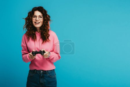 Photo for Happy curly redhead girl playing video game while holding joystick on blue - Royalty Free Image