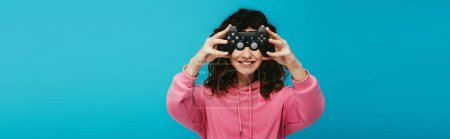 Photo for Panoramic shot of happy curly redhead girl covering face with joystick on blue - Royalty Free Image