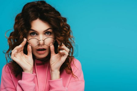 Photo for Surprised curly redhead girl touching glasses isolated on blue - Royalty Free Image