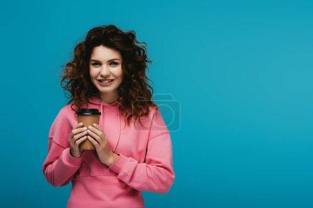 Photo pour Jolie fille heureuse retenant la tasse de papier avec la boisson sur le bleu - image libre de droit