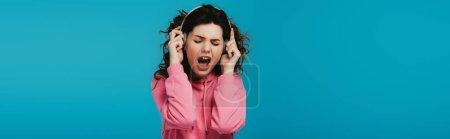 Photo pour Plan panoramique de jolie femme bouclée chantant tout en écoutant de la musique dans les écouteurs sur bleu - image libre de droit