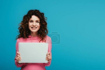 Photo for Cheerful curly redhead girl holding laptop while standing on blue - Royalty Free Image