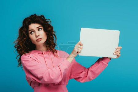 Photo for Upset curly redhead girl holding laptop while standing on blue - Royalty Free Image