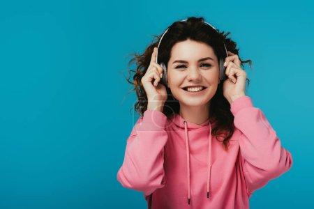 Photo pour Fille heureuse de rousse regardant l'appareil-photo tout en écoutant la musique dans le casque sur le bleu - image libre de droit
