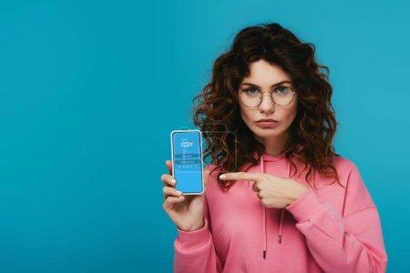 Photo pour Fille rousse bouclée attrayante pointant avec le doigt au smartphone avec l'application de skype sur l'écran isolé sur le bleu - image libre de droit